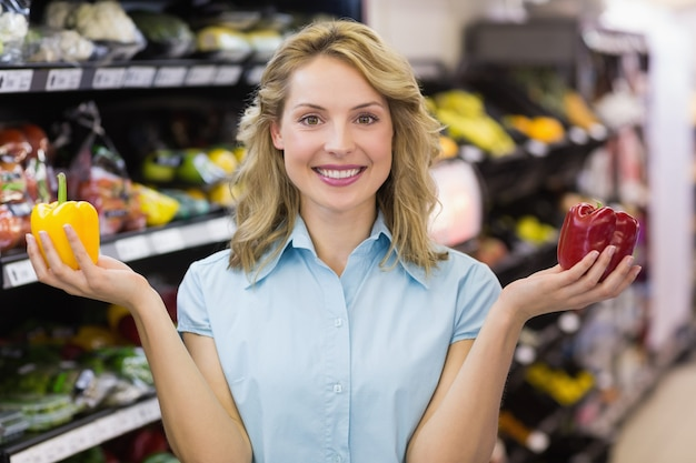 Portrait d'une femme blonde souriante ayant un légume sur ses mains