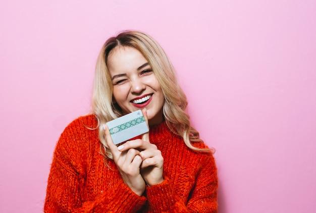 Portrait d'une femme blonde tenant une carte de crédit et souriant dans la chambre sur un mur rose