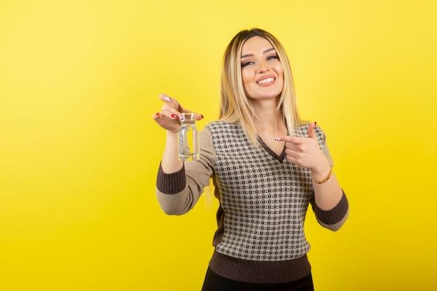 Portrait de femme blonde avec un verre d'eau debout sur jaune.