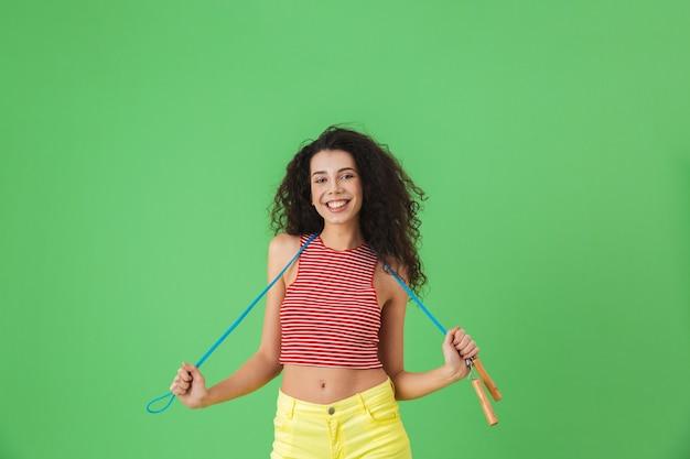 Portrait d'une femme en bonne santé de 20 ans portant des vêtements d'été faisant de l'exercice et faisant des exercices avec une corde à sauter en se tenant debout sur le vert