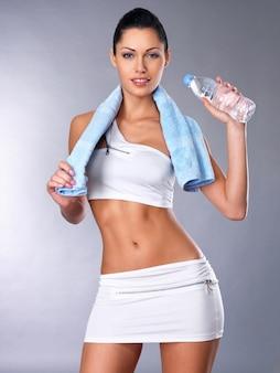 Portrait d'une femme en bonne santé avec une bouteille d'eau et une serviette. concept de mode de vie sain. fille sportive avec beau corps