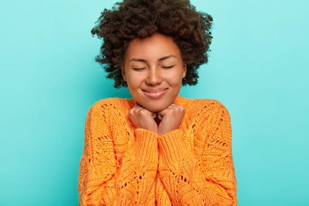 Portrait de femme bouclée aux cheveux croquants, garde les mains sous le menton, ressent du plaisir, porte un pull orange tricoté, isolé sur fond bleu