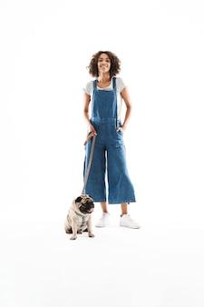 Portrait d'une femme bouclée tenant une laisse et posant avec son chien carlin isolé sur un mur blanc
