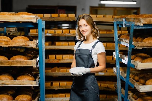 Portrait d'une femme boulangère contre les étagères avec du pain frais dans une boulangerie