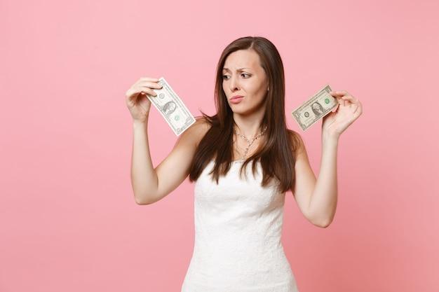 Portrait de femme bouleversée dégoûtée en robe blanche à la recherche de billets d'un dollar