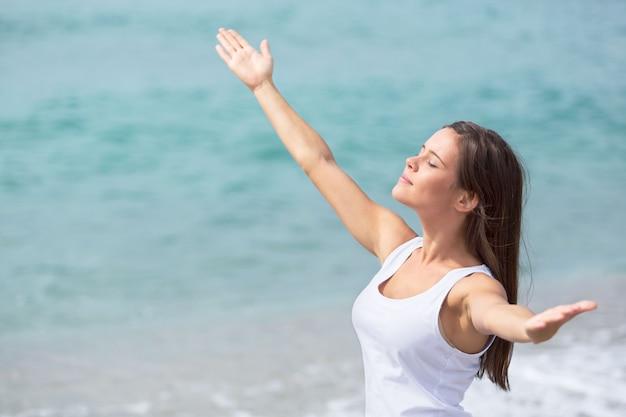 Portrait d'une femme avec les bras ouverts à la plage