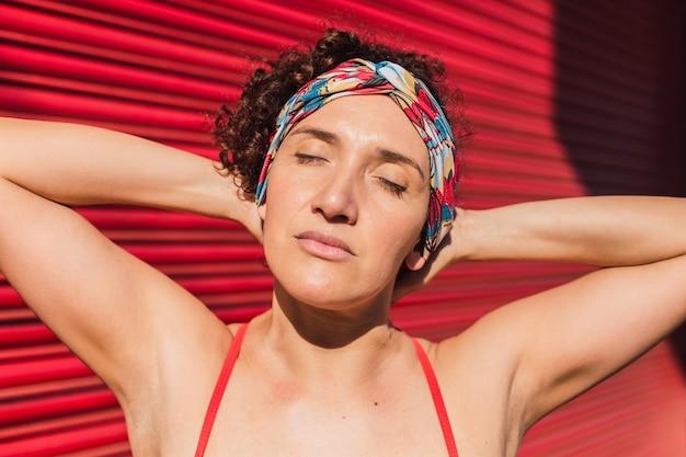 Portrait d'une femme à bras ouverts profitant du soleil sur son visage