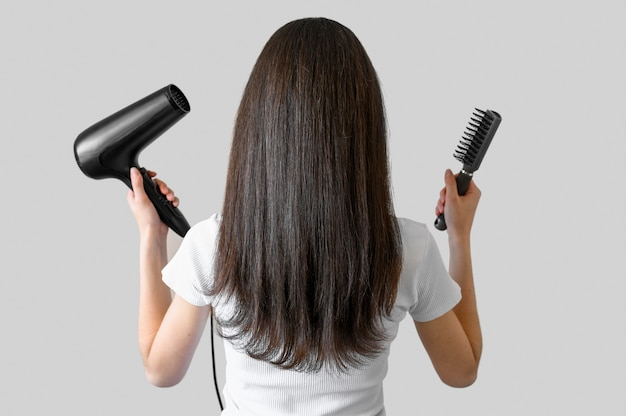 Portrait femme avec brosse et sèche-cheveux