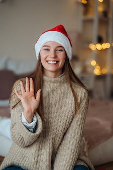 Portrait de femme brune aimable sympathique en bonnet de noel en agitant la main levée et en disant bonjour à la caméra, profitant du temps de noël