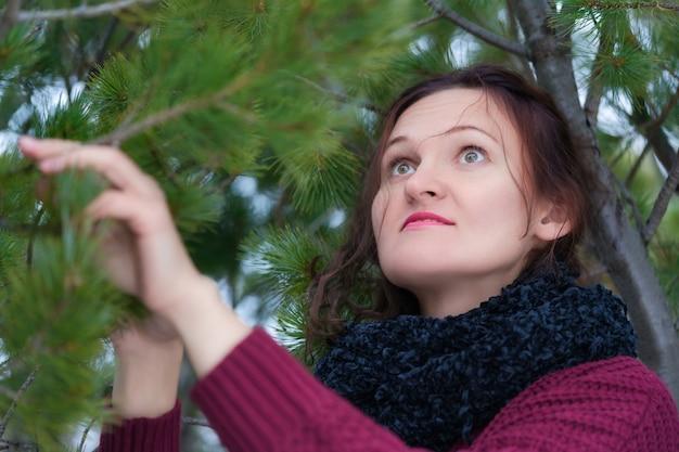 Portrait de femme brune aux cheveux longs et aux yeux bruns debout dans la forêt de pins