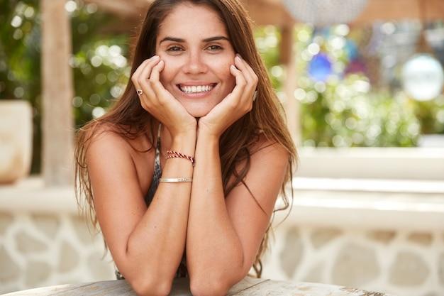 Portrait de femme brune bronzée heureuse avec des cheveux longs, des dents blanches parfaites et un sourire agréable, se trouve contre l'intérieur du café.