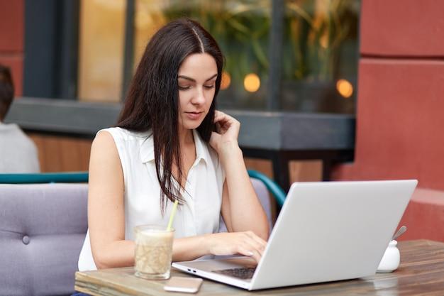 Portrait de femme brune concentrée travaille sur un projet d'entreprise tout en utilisant un ordinateur portable moderne, concentré sur l'écran, les boissons, assis contre l'intérieur du café, des messages avec des amis