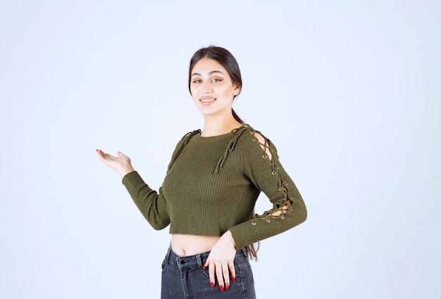 Portrait de femme brune debout et montrant un espace vide.