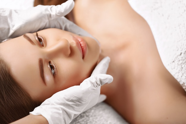 Portrait de femme brune douce et belle prenant un massage de la tête