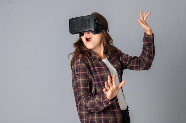 Portrait de femme brune drôle testant un casque de réalité virtuelle en studio sur mur gris