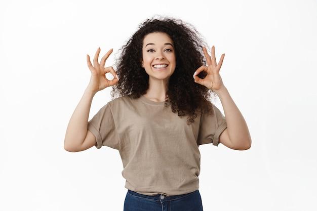 Portrait de femme brune frisée fière et heureuse sur le blanc