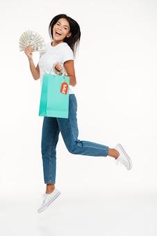 Portrait d'une femme brune heureuse sautant