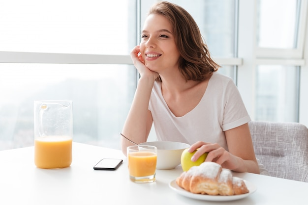 Portrait de femme brune joyeuse et rêveuse tenant sa tête tout en prenant son petit déjeuner à la table de la cuisine