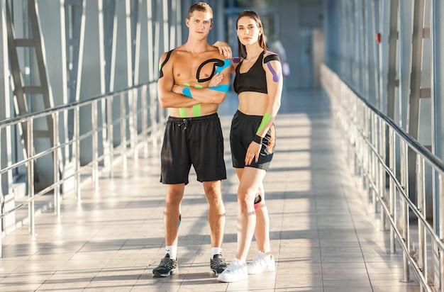 Portrait de femme brune musclée avec les bras croisés et l'homme. athlètes de jeunes couples posant à l'intérieur, kinesiotaping coloré sur le corps, intérieur futuriste.