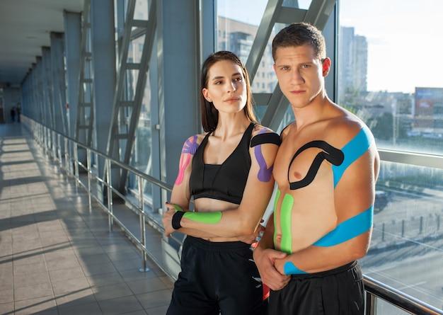 Portrait de femme brune musclée avec les bras croisés et homme regardant la caméra avec un visage fort. athlètes de jeune couple posant à l'intérieur, kinesiotaping coloré sur le corps, intérieur futuriste.