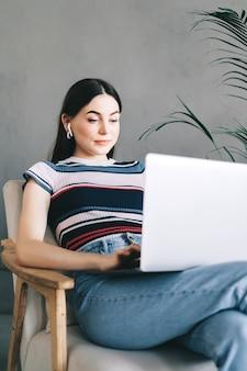 Portrait de femme brune, pigiste travaillant à distance à la maison, regardant l'écran du portable