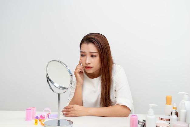 Portrait de femme brune regardant son visage dans un miroir