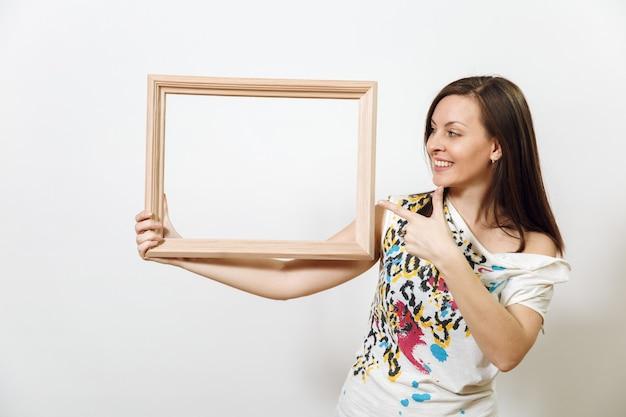 Le portrait d'une femme brune souriante heureuse debout et tenant un cadre en bois vide sur fond blanc. avec place pour le texte pour la publicité.