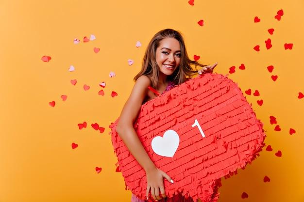 Portrait de femme brune souriante obsédée par les réseaux sociaux. portrait intérieur de fille glamour debout sur jaune sous des confettis.