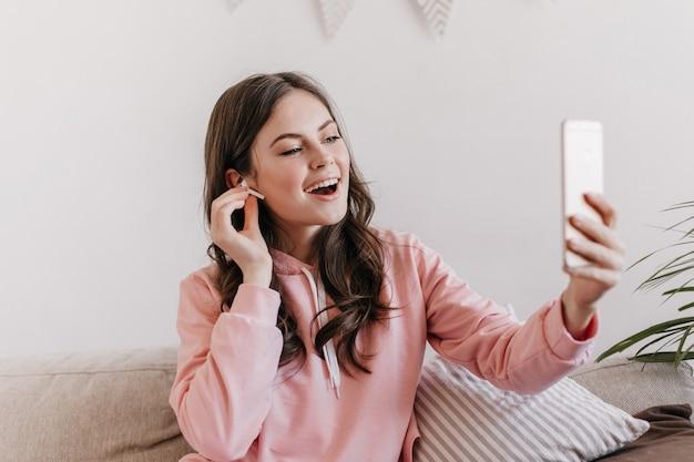 Portrait de femme brune en sweat à capuche rose parlant via lien vidéo dans le smartphone