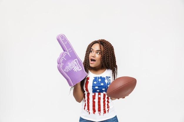 Portrait d'une femme brune tenant un gant de fan numéro un et un ballon de rugby en position debout isolée contre un mur blanc