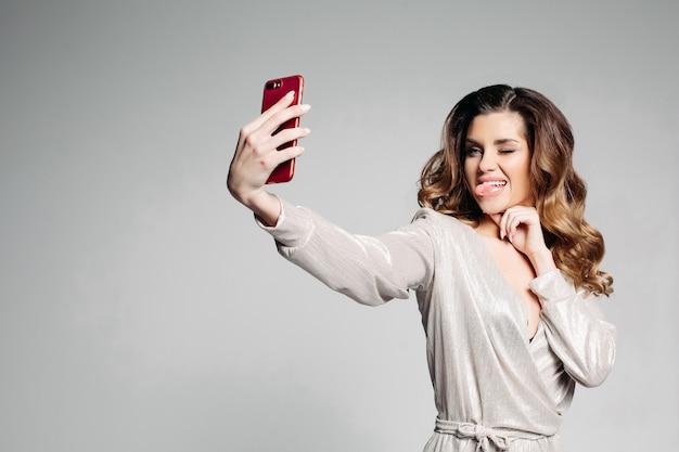 Portrait d'une femme brune vêtue d'une élégante robe grise, avec maquillage et coiffure, fait selfie montrant sa langue et fisting ses yeux, pour les réseaux sociaux.