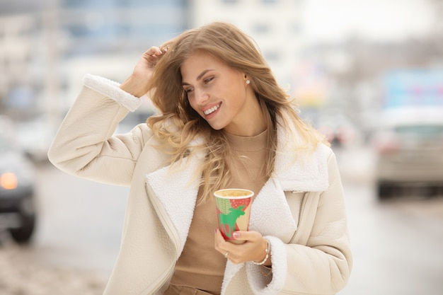 Portrait de femme buvant du café en hiver en plein air.