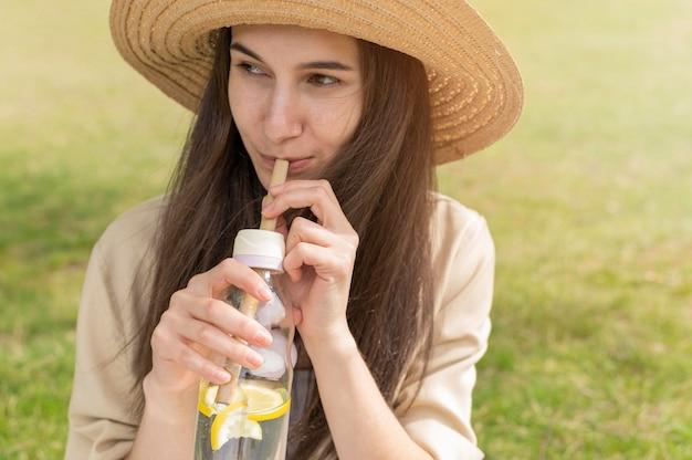 Portrait de femme buvant de l'eau avec des citrons