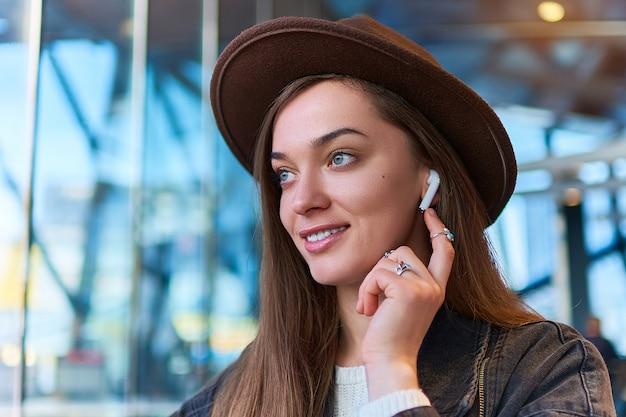 Portrait de femme casual hipster branché élégant en chapeau avec un casque sans fil. mode de vie numérique et personnes modernes