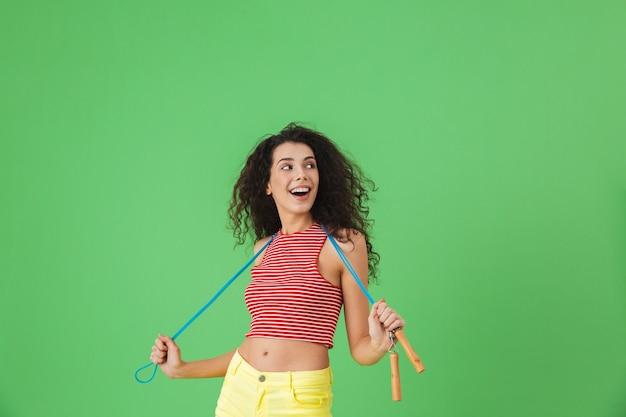 Portrait d'une femme caucasienne de 20 ans portant des vêtements d'été s'entrainant et faisant des exercices avec une corde à sauter en se tenant debout sur le vert
