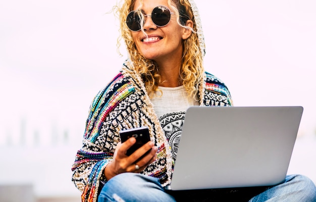 Portrait d'une femme caucasienne adulte joyeuse travaillant en plein air avec téléphone et ordinateur portable en technologie d'itinérance