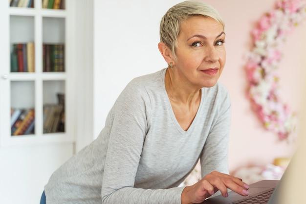 Portrait d'une femme caucasienne âgée moderne avec une coupe de cheveux courte posant