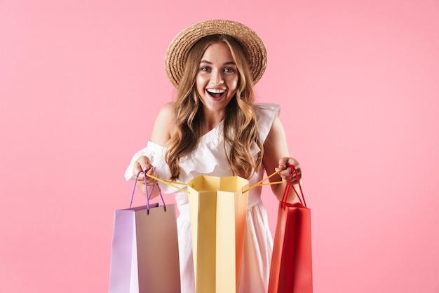 Portrait d'une femme caucasienne étonnée portant un chapeau de paille se demandant et tenant des sacs à provisions isolés sur un mur rose