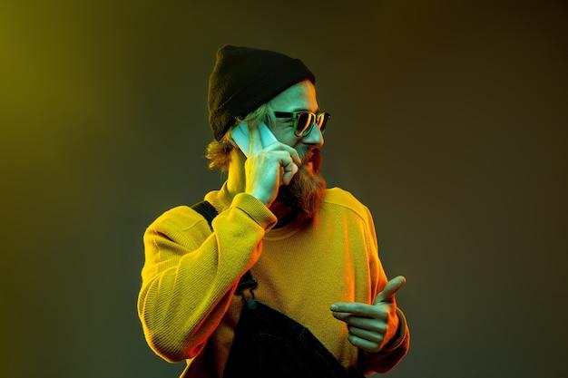 Portrait de femme caucasienne sur fond de studio dégradé en néon. beau modèle masculin avec un style hipster dans des verres. concept d'émotions humaines, expression faciale, ventes, publicité. parler au téléphone.