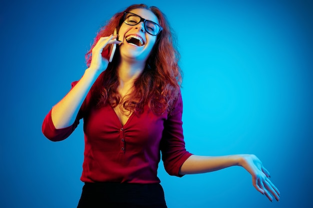 Portrait de femme caucasienne isolé sur fond bleu studio en néon. beau modèle féminin aux cheveux rouges en casual. concept d'émotions humaines, expression faciale, ventes, publicité. parler au téléphone.