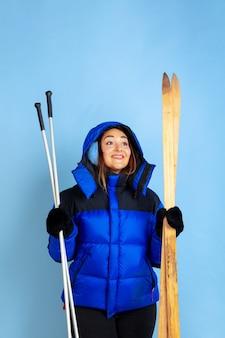 Portrait de femme caucasienne isolé sur fond bleu studio, thème hiver