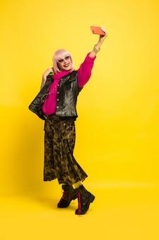 Portrait de femme caucasienne isolé sur fond de studio jaune, influenceur être comme