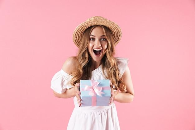 Portrait d'une femme caucasienne ravie portant un chapeau de paille se demandant et tenant une boîte présente isolée sur un mur rose