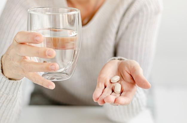 Portrait d'une femme caucasienne sesior tenant une pilule et un verre d'eau. espace copie
