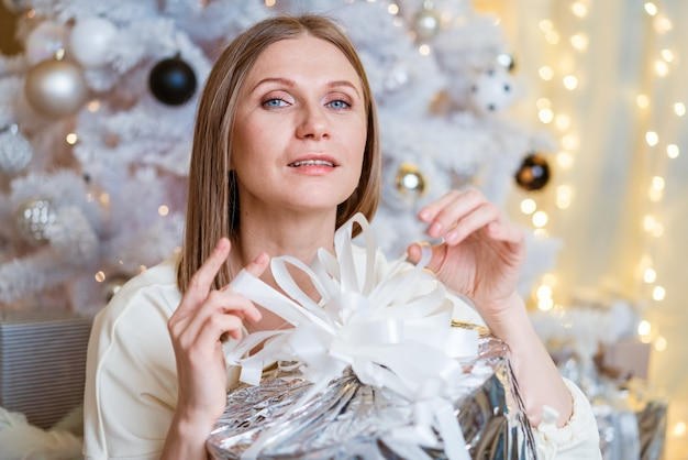 Portrait d'une femme caucasienne souriante vêtue d'une robe légère et tenant une boîte-cadeau en argent près d'un arbre un jeune...