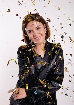 Portrait de femme célébrant avec des confettis
