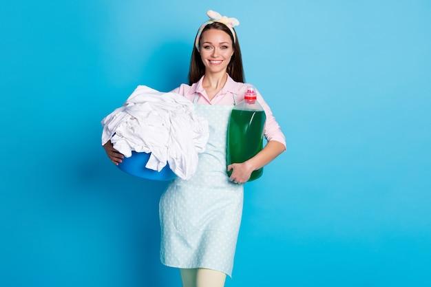 Portrait d'une femme de chambre joyeuse portant dans les mains une lessive au savon en poudre liquide