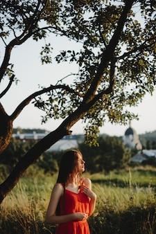 Portrait de femme charmante femme en robe rouge se dresse sous l'ol