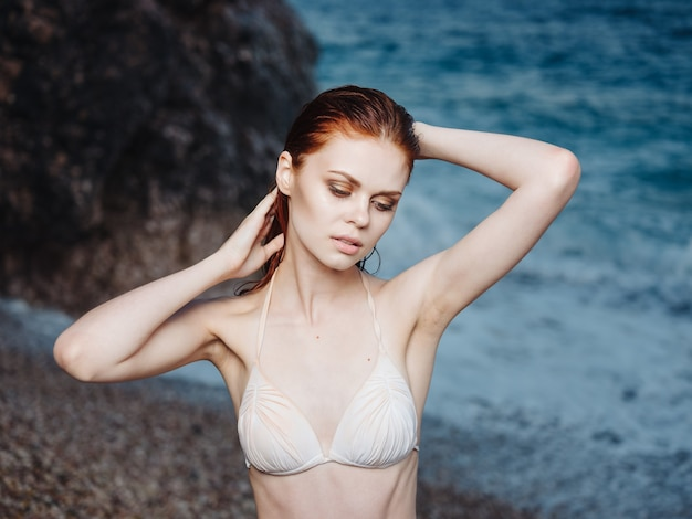 Portrait de femme charmante modèle de maillot de bain blanc et plage de mousse blanche mer bleue. photo de haute qualité