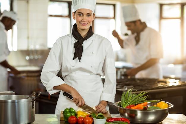 Portrait de femme chef coupe des légumes